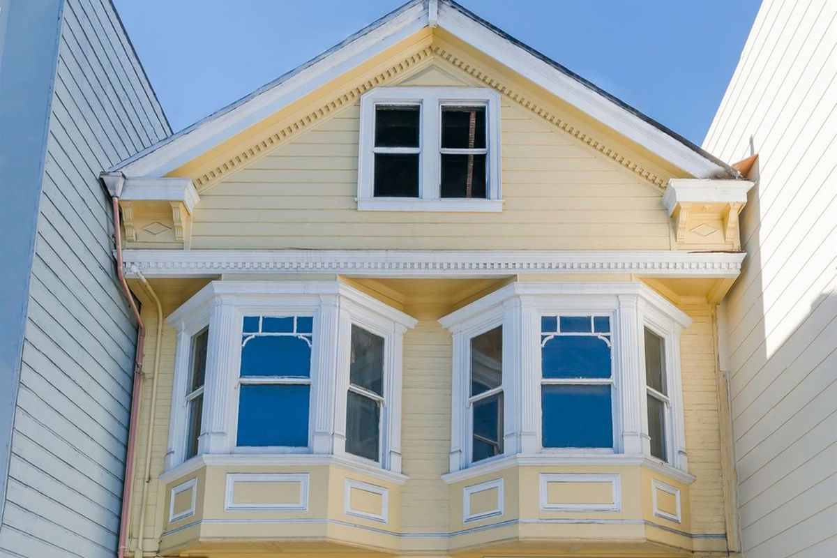 The undamaged looking facade of a yellow Richmond district Victorian home.