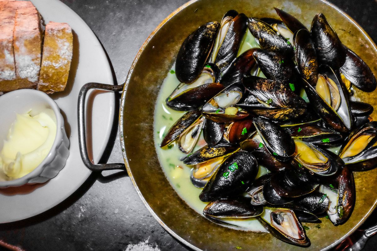 Big silver skillet of mussels in a buttery sauce, with a side of bread