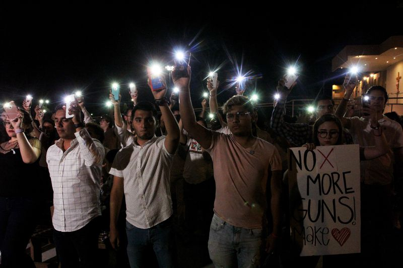 """People at a vigil hold up their mobile phones with the flashlight on. One woman carries a sign that reads, """"No more guns."""""""