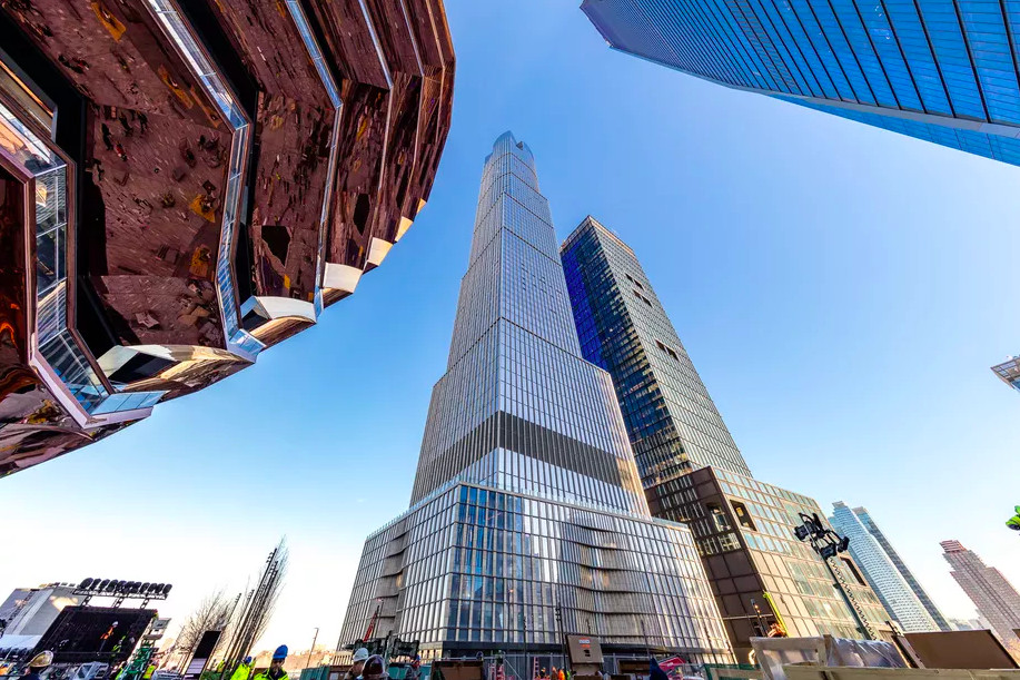 An image of a glassy skyscraper from below.