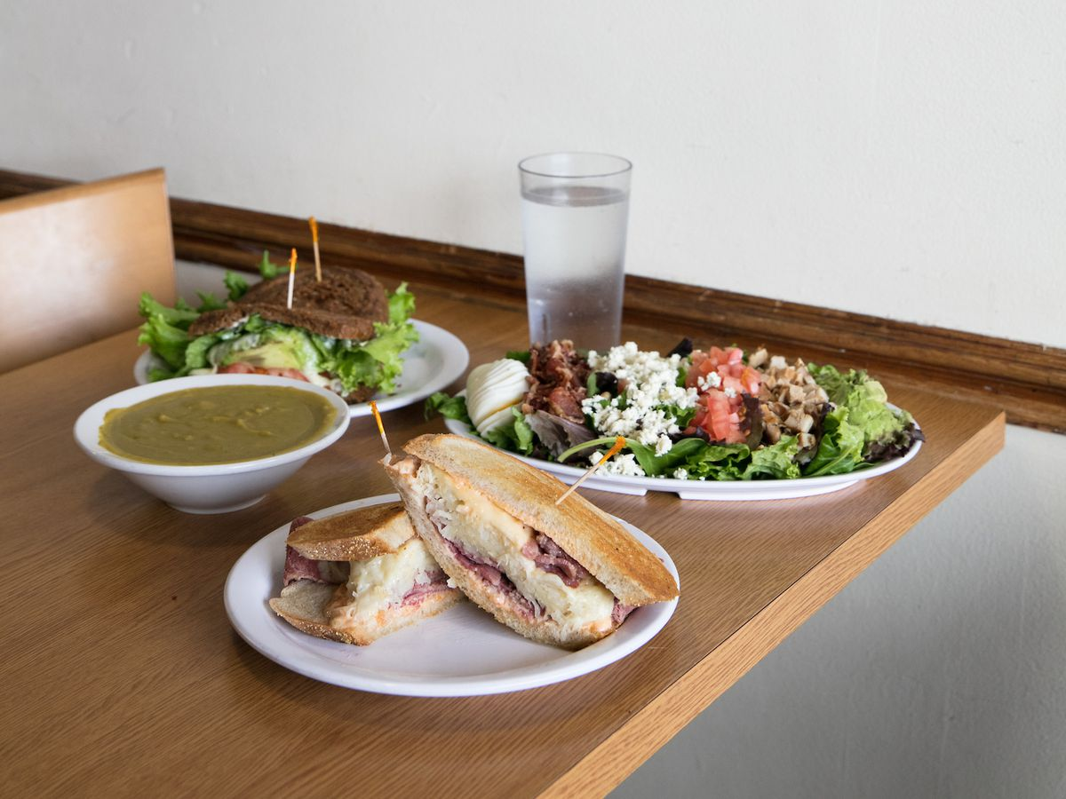 A corned beef sandwich in the foreground surrounded by a green-colored soup, a veggie sandwich on dark pumpernickel bread, and a cobb salad