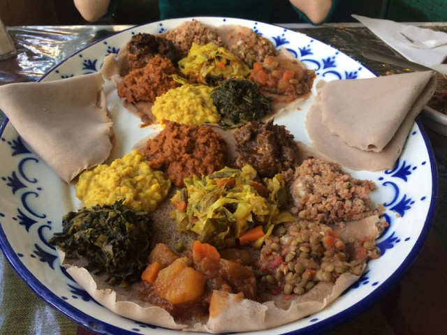 Clumbs of bright Ethiopian food with folded injera on a plate