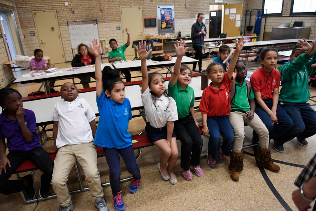 Aliyah Biggs, 6, second from left and Ashli Ramos-Rosales, 8, raise their hands to take part in an after-school talent show at Ashley Elementary in Denver.