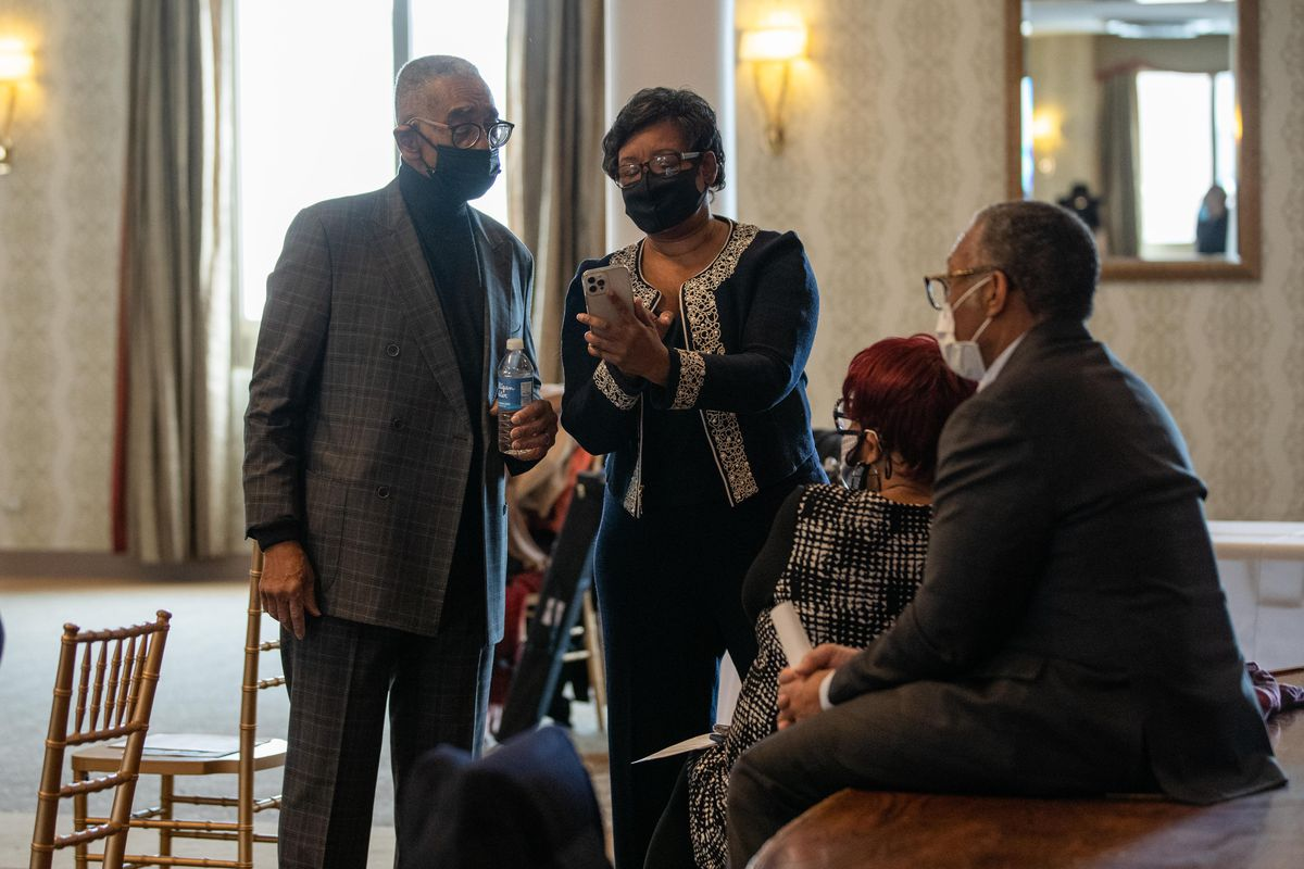 U.S. Rep. Bobby Rush looks at Ald. Michelle Harris' (8th) phone before a news conference last week.
