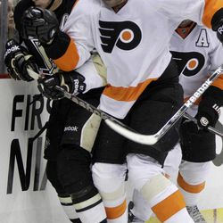 Pittsburgh Penguins' Sidney Crosby, left, is checked into the boards by Philadelphia Flyers' Pavel Kubina (13) in the second period of an NHL hockey game in Pittsburgh Saturday, April 7, 2012. The Penguins won 5-2.