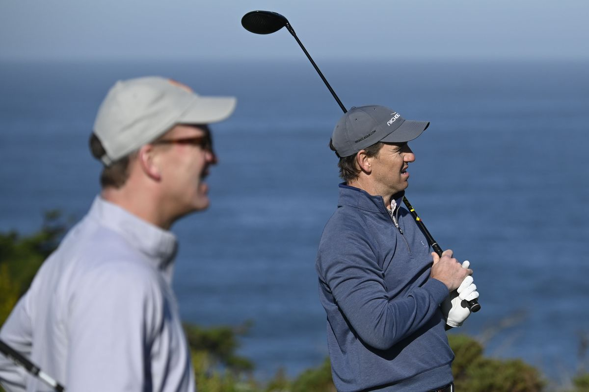 Eli Manning (right) hits his tee shot in front of Peyton Manning (left) on the fourth hole during the first round of the AT&T Pebble Beach Pro-Am golf tournament at Spyglass Hill Golf Course.