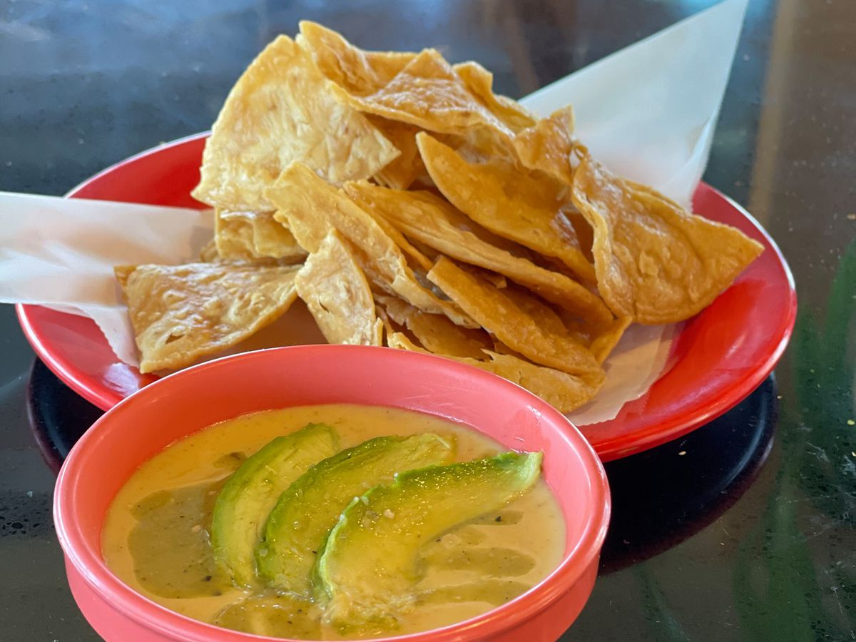 Queso in a pink bowl topped with avocado and thick-cut chips