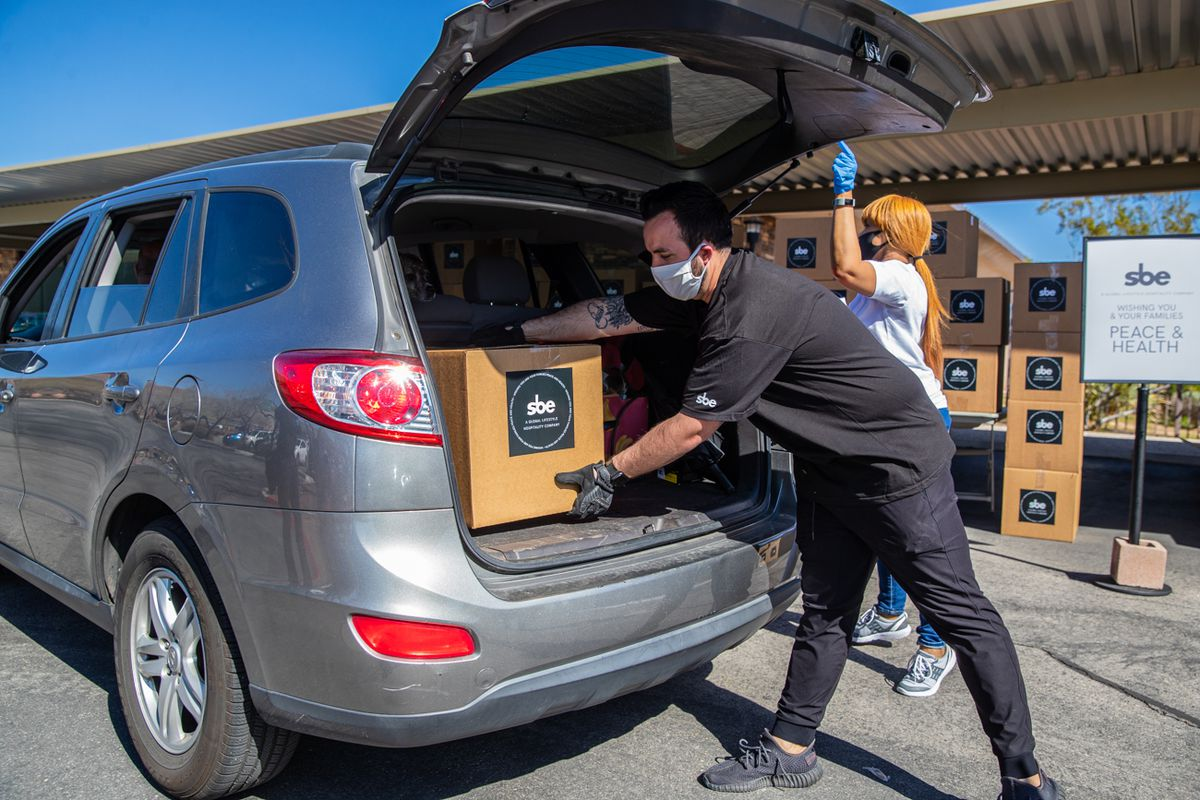 Employees at sbe load a care package into the back of a vehicle.