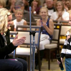 Elle Faulkner, 7, gets applause from her mother, Summer, after competing in national anthem tryouts at EnergySolutions Arena on Friday, Oct. 4, 2013. The winners will perform the anthem prior to each Utah Jazz home game during the 2013-2014 season.