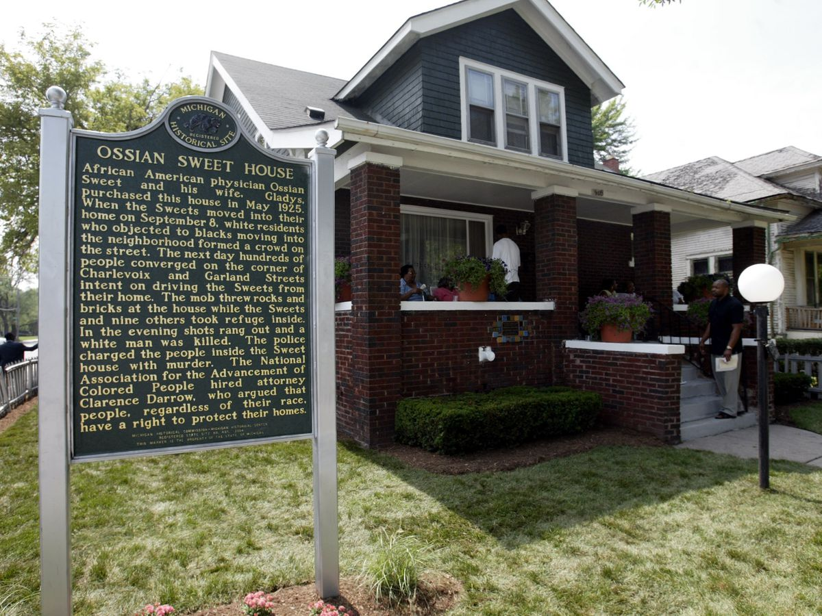 """A green plaque with gold lettering stands in the yard of a two-story brick home. The heading of the plaque reads """"Ossian Sweet House."""""""