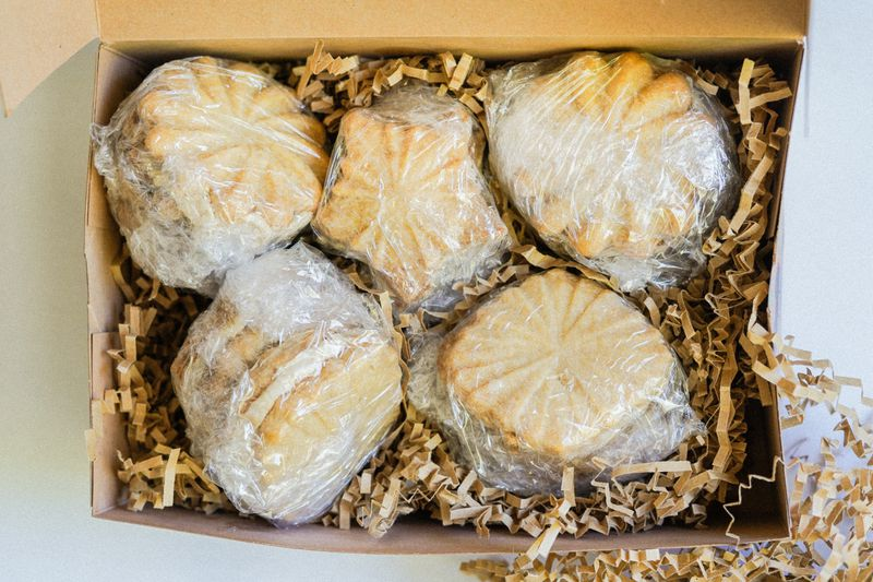 Sandwich cookies in cutout shapes, wrapped in plastic wrap and placed in a cardboard box with crinkle paper.