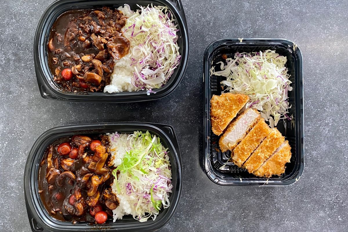 Two versions of very dark Japanese black curry, served in a takeout container with rice, and a side of sliced tonkatsu (fried pork cutlet)