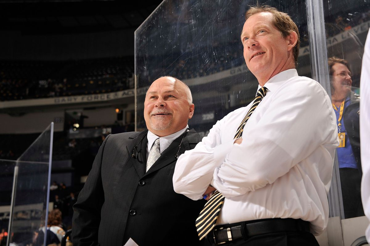 Head coach Barry Trotz and assistant coach Phil Housley of the Nashville Predators watch their team warmup prior to a game against the Tampa Bay Lightning at Bridgestone Arena on September 24, 2013 in Nashville, Tennessee.