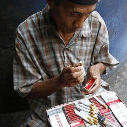 A cigarette vendor packs cigarettes to be sold individually for one US cent per stick in Jakarta, Indonesia, Tuesday, Sept. 11, 2012. Indonesian men rank as the world's top smokers, with two out of three of them lighting up in a country where cigarettes cost pennies and tobacco advertising is everywhere.