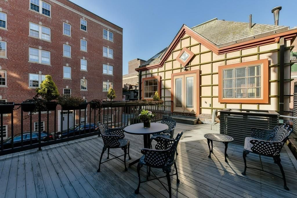 A spacious roof deck with a table and chairs as well as a bench.