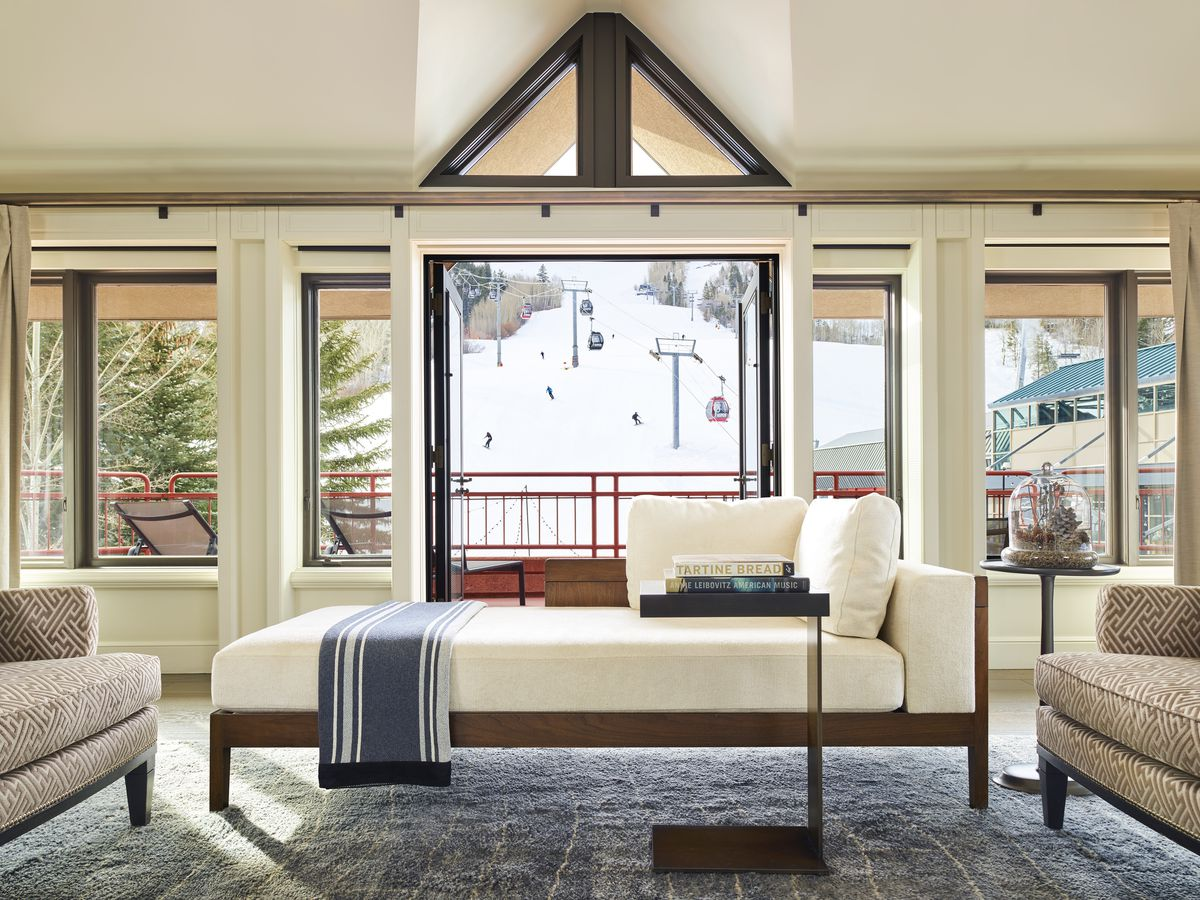 A cream day bed with a striped blue blanket sits in a light and airy living room. Beige couches are on either side of the bed, and beyond the bed there is a window with views of a ski slope.