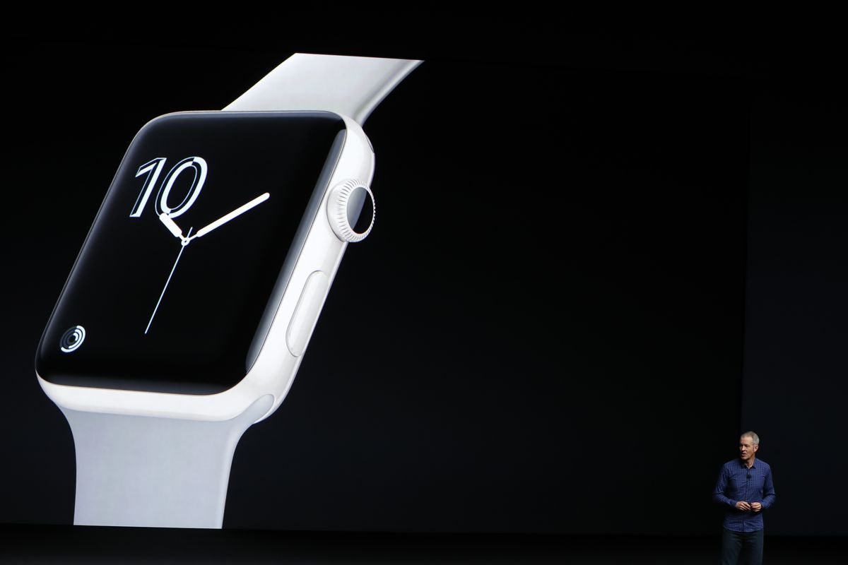 Apple COO Jeff Williams introduces the new Apple Watch Series 2 smartwatch in ceramic during a launch event on September 7, 2016 in San Francisco, California. Williams is a tiny figure in the bottom right of the image. The background is black. A projected