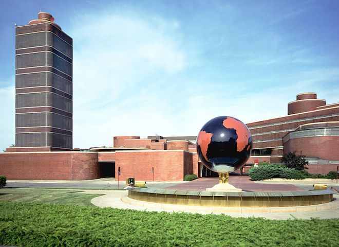 The Johnson Wax Headquarters by Frank Lloyd Wright. The building is red brick with multiple levels and terraces. There is a red and black globe in front of the building.