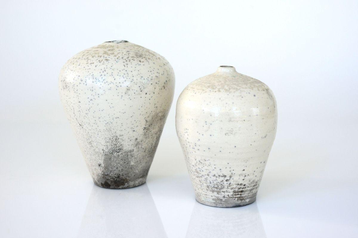 White vases/vessels with black patterns splattered from bottom