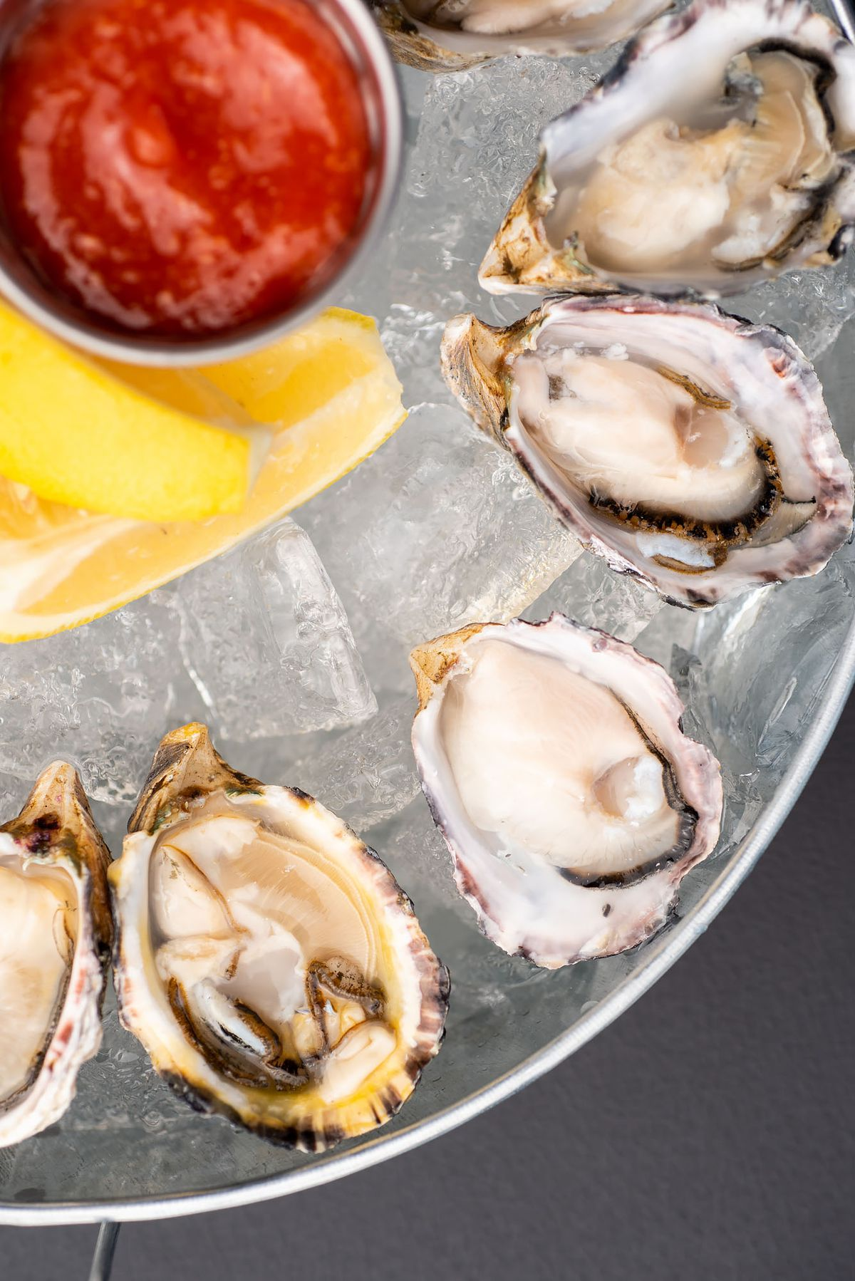 Oysters on ice on a metal tray with mignonette