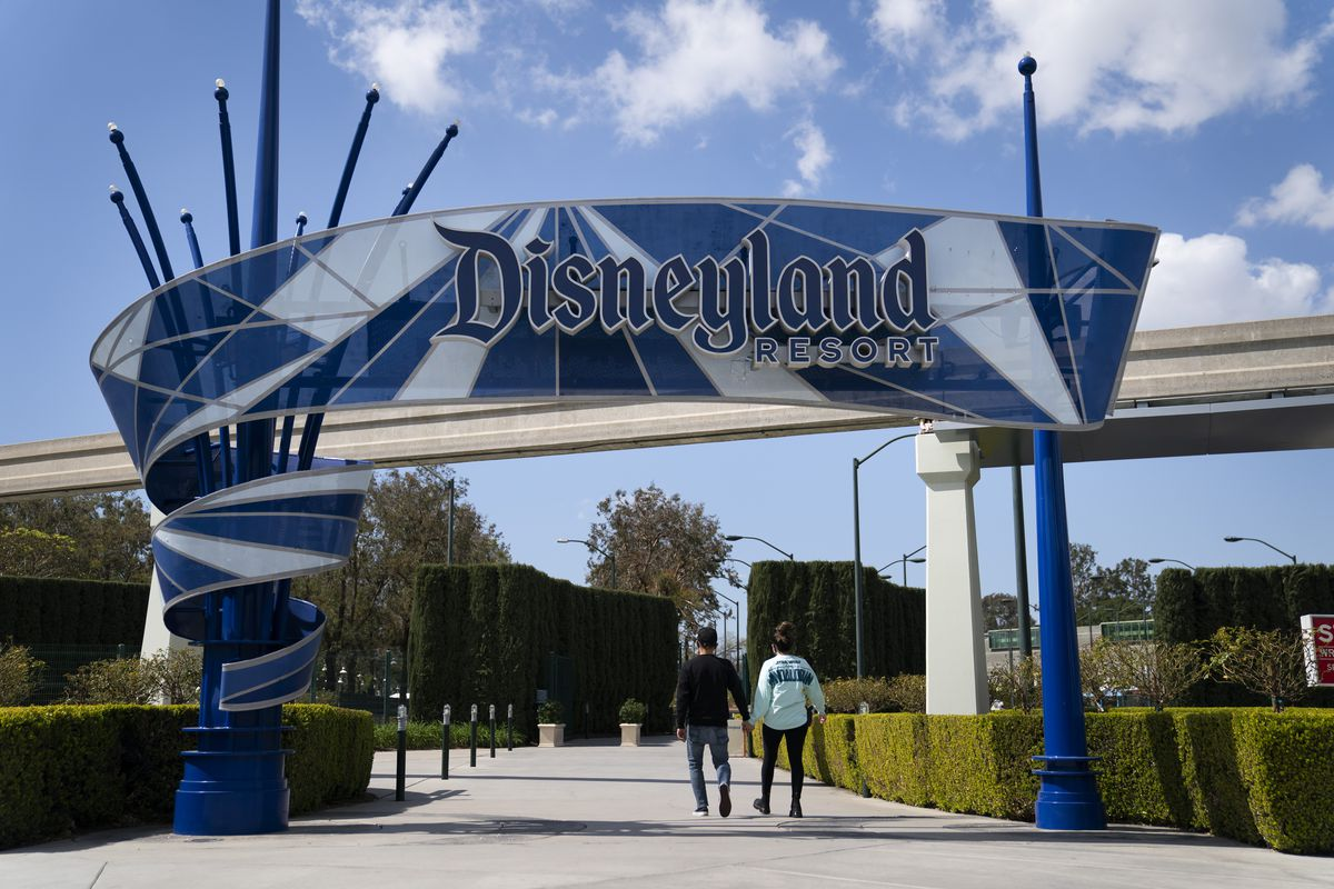 Two visitors enter Disneyland Resort in Anaheim, Calif., Tuesday, March 9, 2021. Disneyland employees — called Cast Members — may look a little different compared to when you last saw them.