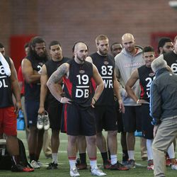NFL hopefuls listen for instruction before doing drills for pro scouts during Utah pro football day at the University of Utah Wednesday, March 19, 2014, in Salt Lake City.