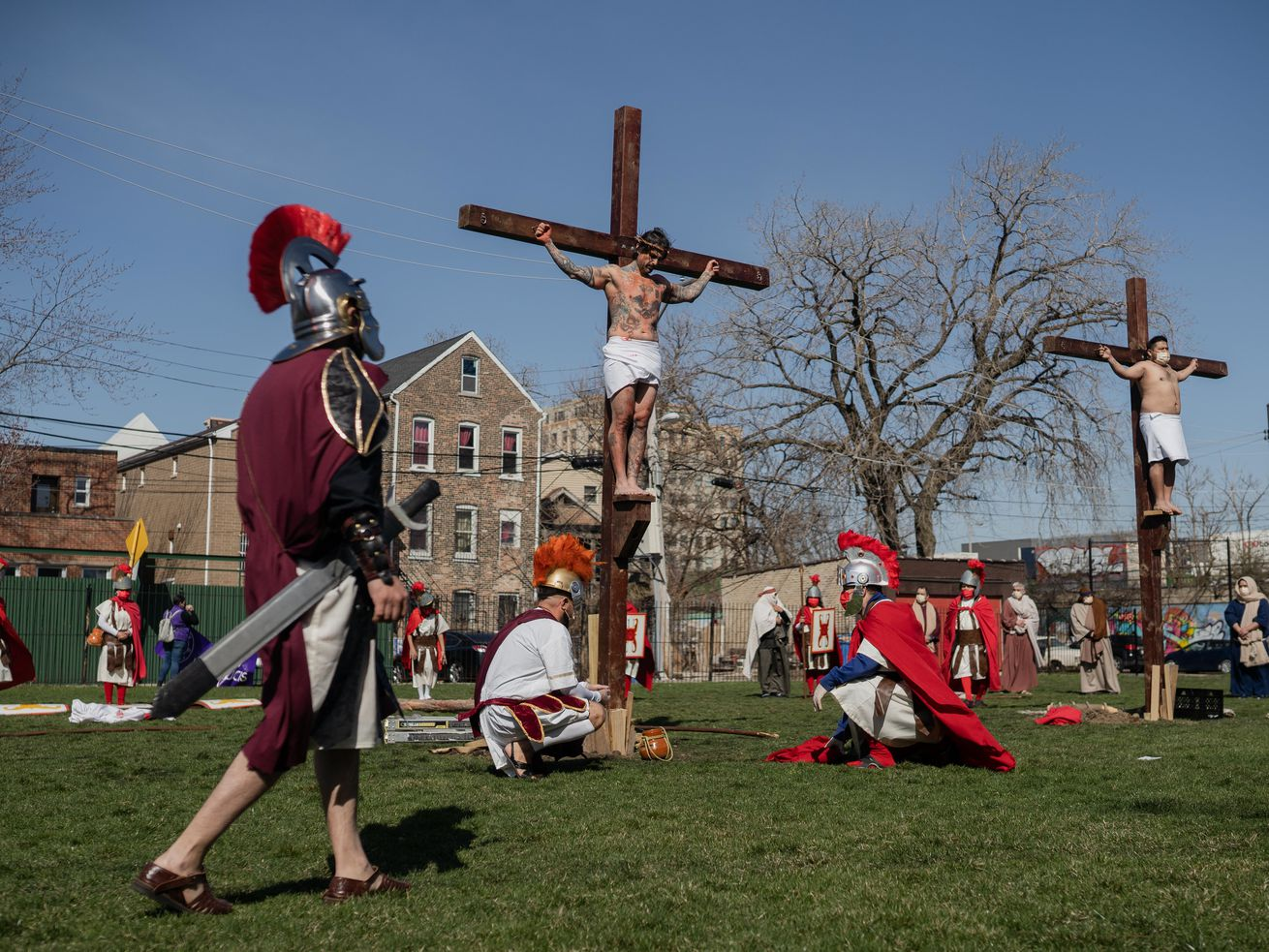 Isaac Pucio, who plays Jesus Christ, acts as if he is crucified during Via Crucis on the field of St. Procopius Catholic Church in Pilsen, Friday morning, April 2, 2021. The annual Via Crucis is a Good Friday tradition that reenacts the Stations of the Cross, a Catholic devotion that recounts Jesus' passion and death.