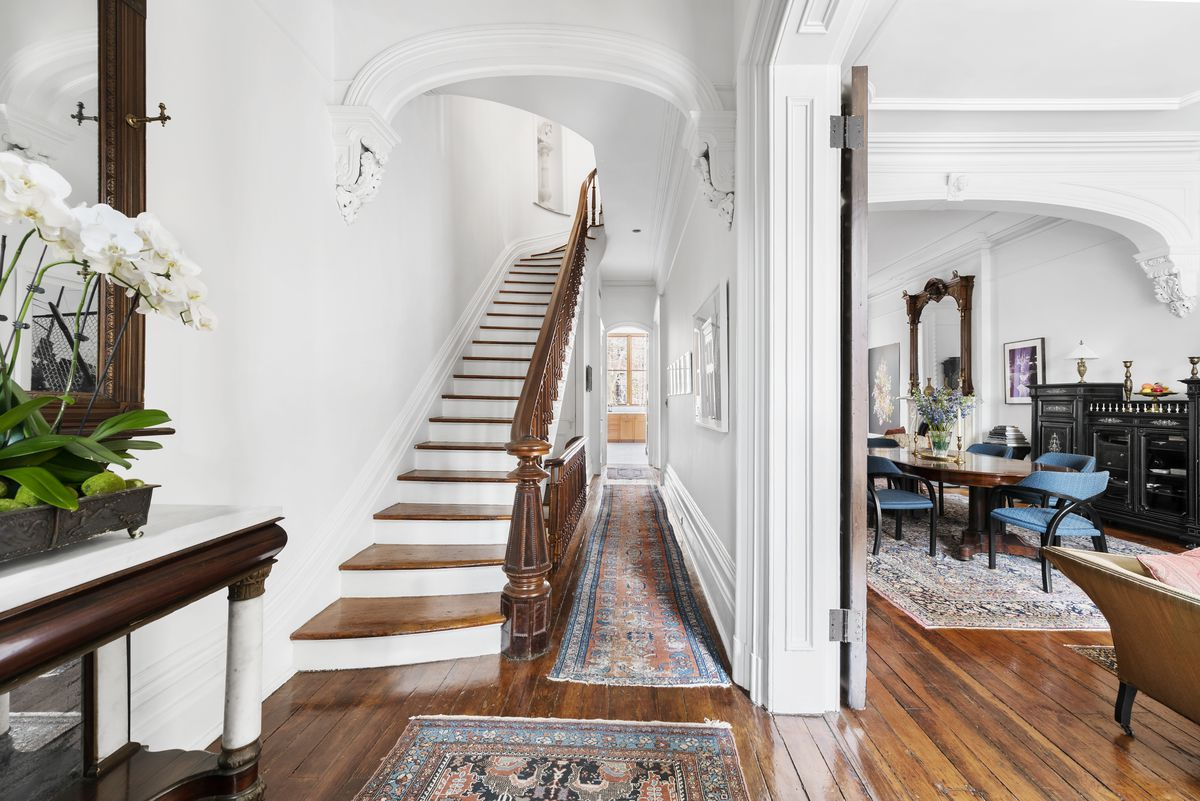 A foyer with a wooden staircase, hardwood floors, arched entryways, and crown moldings.