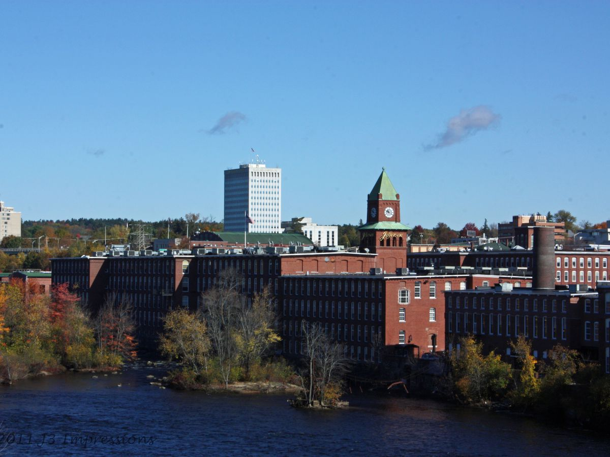 A fall view of a New England skyline, including a large brick building along a river.