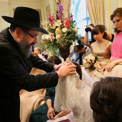 Rabbi Benny Zippel blesses his daughter, Chaya Zippel, during the badeken, or veiling ceremony, before she marries Rabbi Mendy Cohen in a traditional Chabad Lubavitch Jewish wedding at the Grand America Hotel in Salt Lake City on Monday, Sept. 12, 2016.