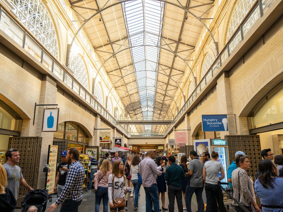 The interior of the Ferry Building Marketplace. The ceiling is high and arched. Thee are many people walking in the main aisle. There is a skylight running along the ceiling.