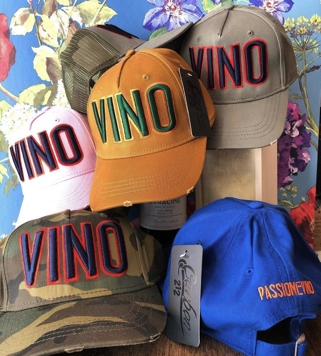 A range of colourful baseball caps with the word VINO embossed on the front