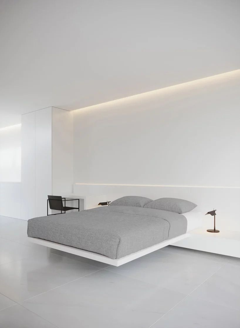 Floating bed with gray bedding attached to wall in bedroom.