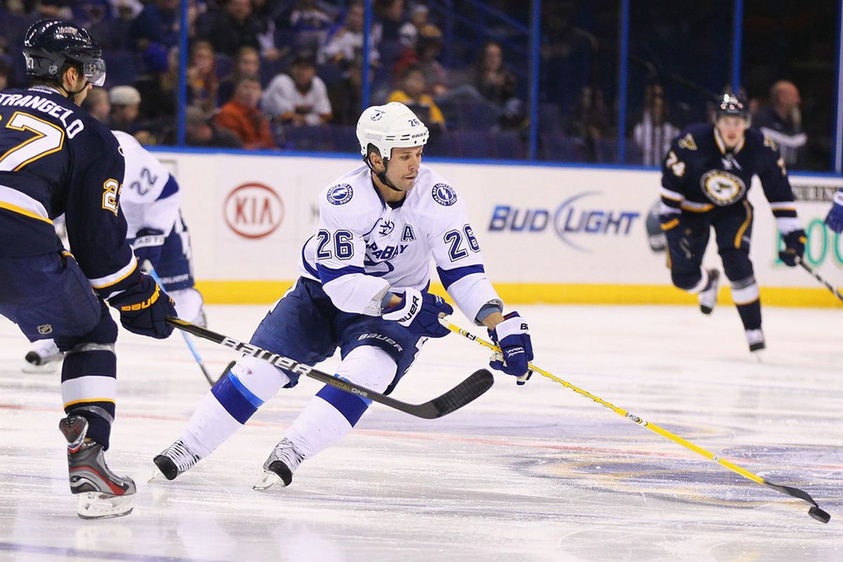 ST. LOUIS, MO - NOVEMBER 12:  Martin St. Louis #26 of the Tampa Bay Lightning moves the puck up ice against the St. Louis Blues at the Scottrade Center  on November 12, 2011 in St. Louis, Missouri.  (Photo by Dilip Vishwanat/Getty Images)