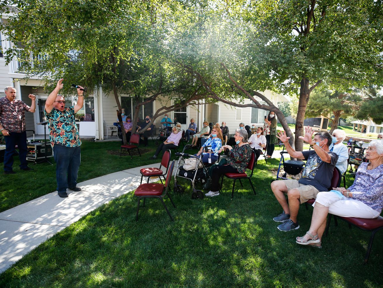 Musicians from the local musical group SunShade n' Rain sing while interacting with senior citizens during an outdoor concert at Solstice Senior Living in Sandy on Saturday, Sept. 12, 2020.