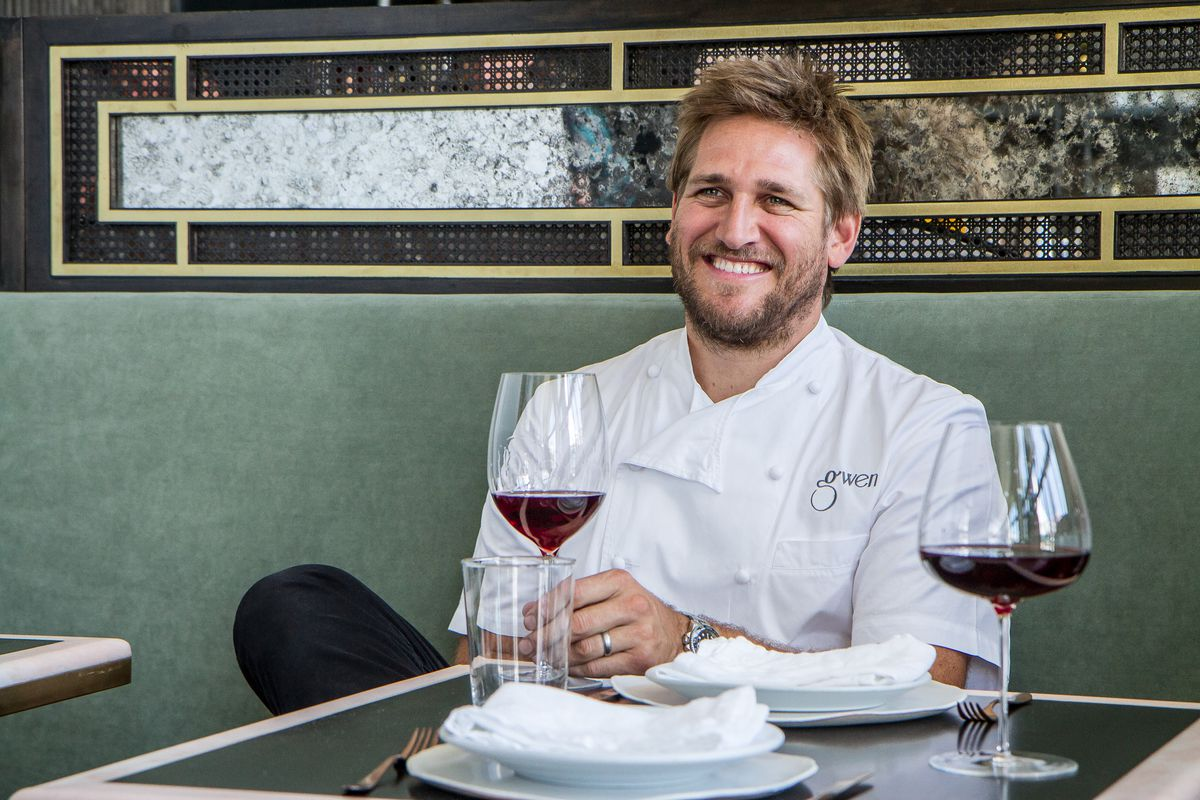 Photo of Curtis Stone sitting at a table holding a glass of wine and wearing chefs coat.