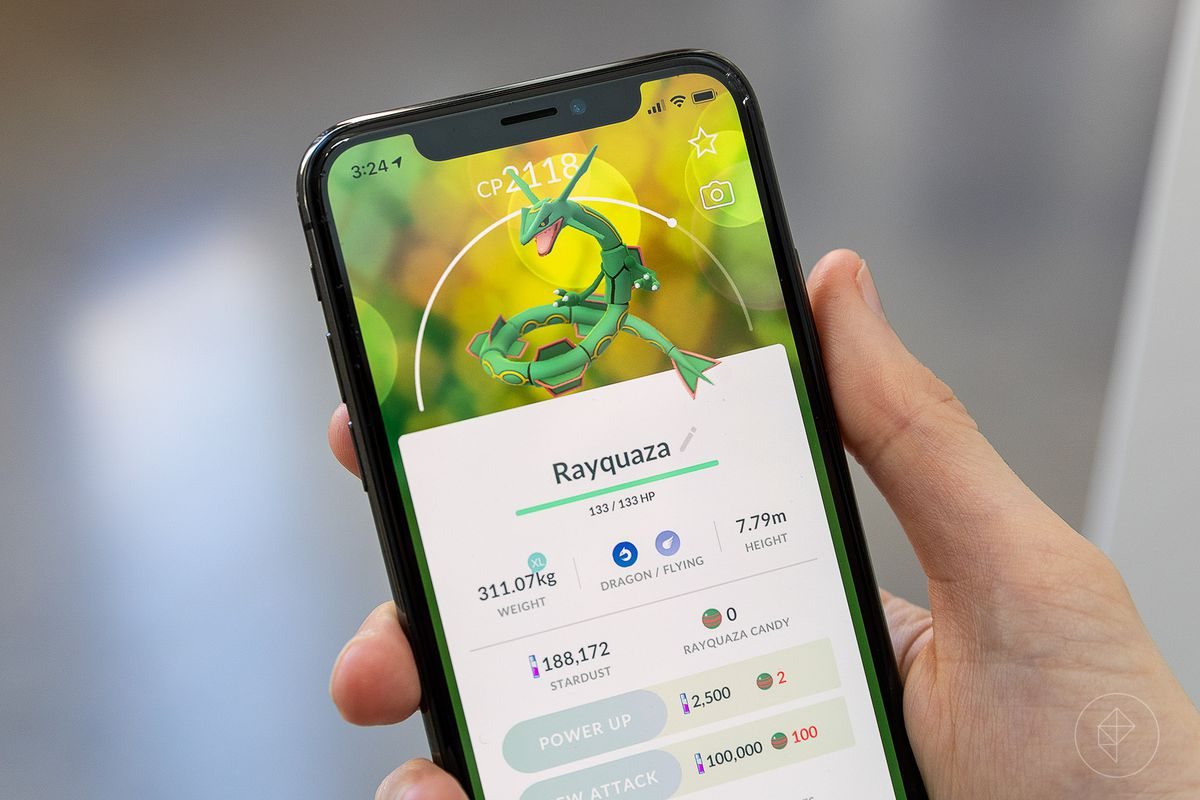A hand holds up an iPhone with Rayquaza's Pokémon Go stat screen