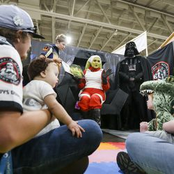 "Ben Driggs, left, and his daughter Molly Driggs, 9 months, listen to ""Story Time in a Galaxy Far Far Away"" alongside Tiffany Tyler, right, and her son Lincoln Tyler, 6 months, during the first day of FanX at the Salt Palace Convention Center in Salt Lake City on Thursday, Sept. 5, 2019."