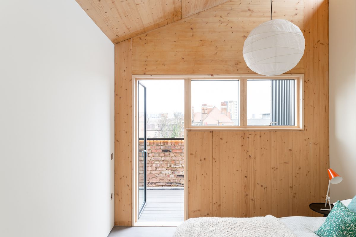Bedroom with white wall and wooden wall.