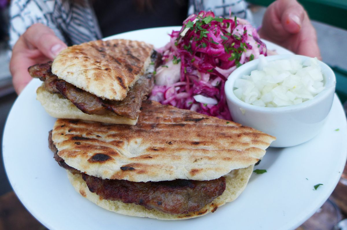 Ground meat patty on a pita with chopped onions and purple salad on the side.
