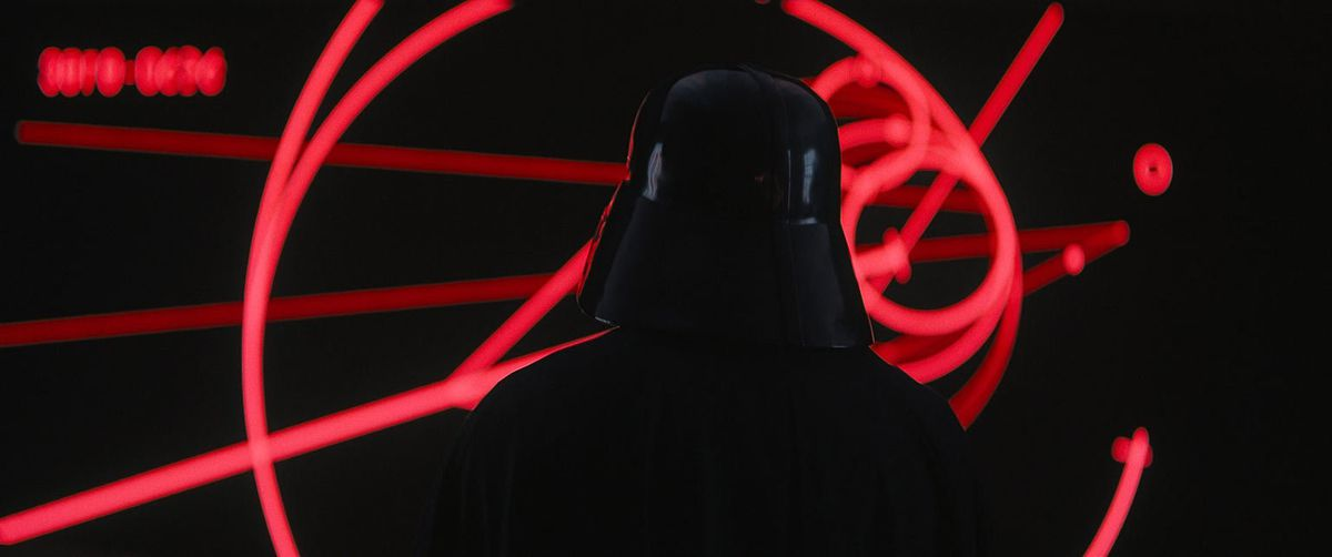 Darth Vader stands in front of a display in Rogue One