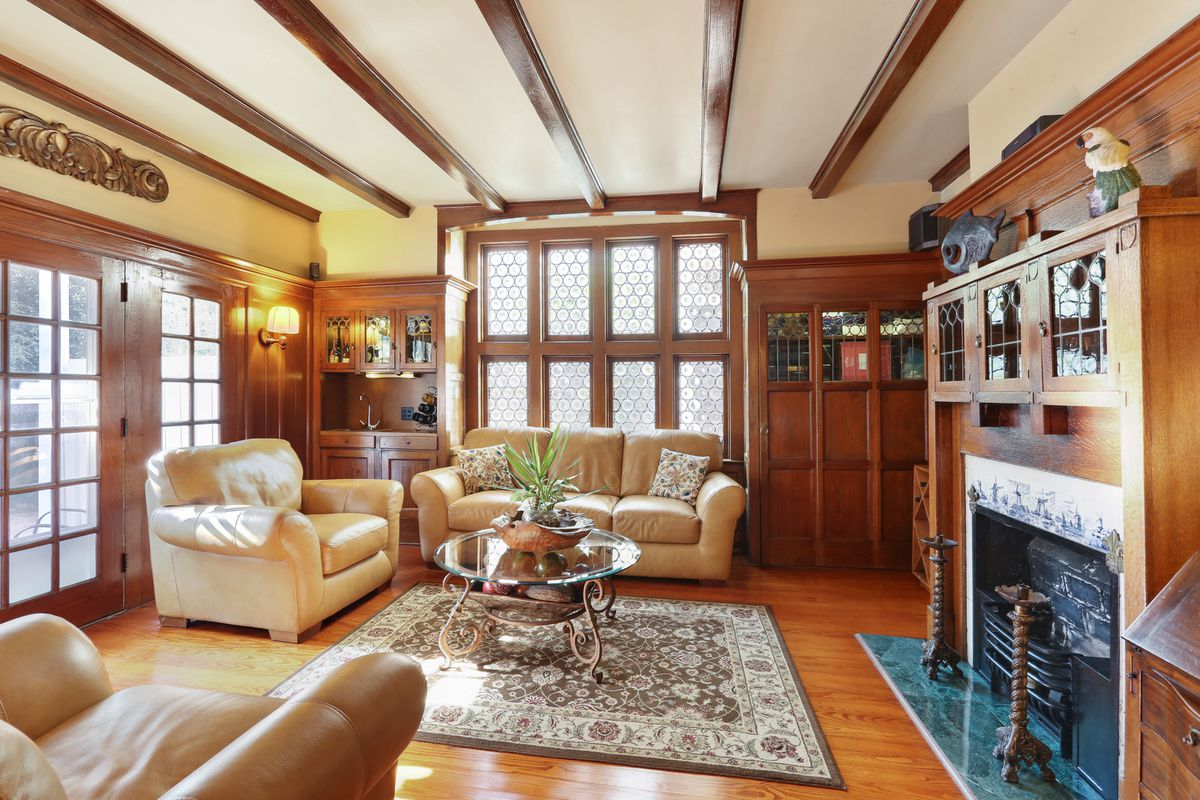 A wood-paneled room with overhead beams and a fireplace