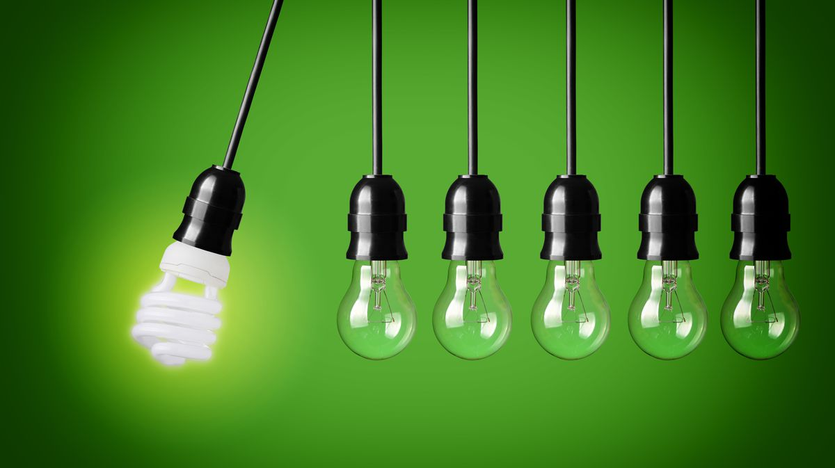 A series of incandescent light bulbs with a single fluorescent bulb swinging toward them.