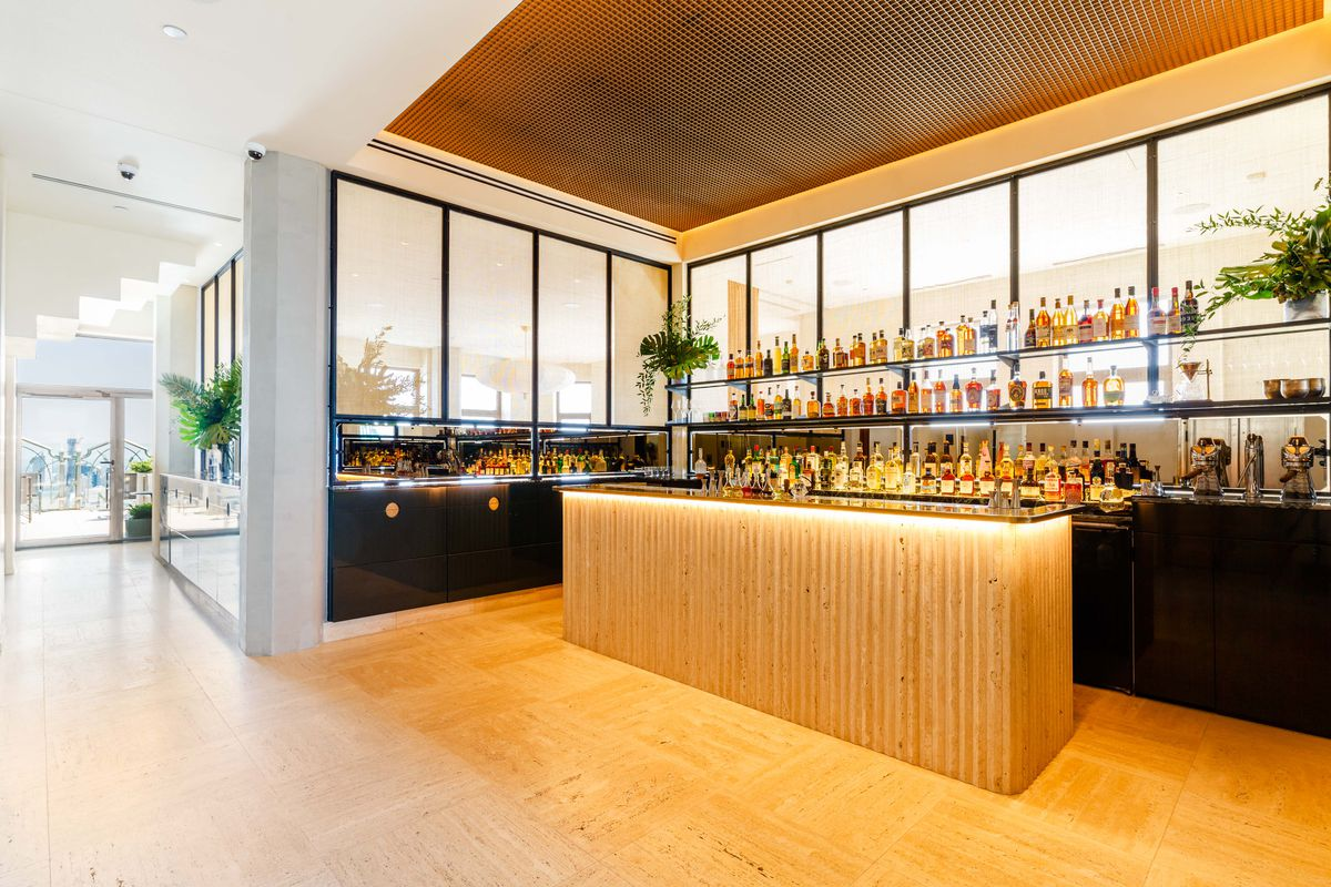 A light wooden bar surrounded on three sides with walls stocked with liquor bottles. A hallway leads to an outdoor terrace on the right.