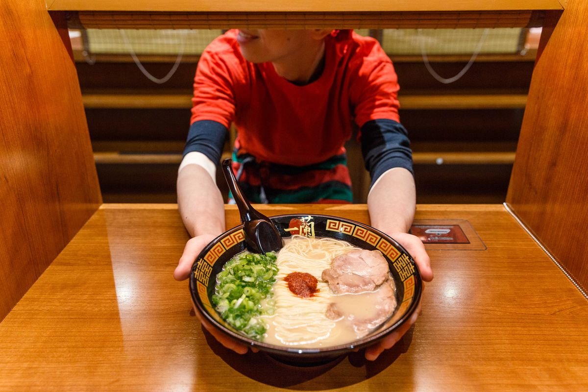 A man hands off a bowl of ramen to the camera