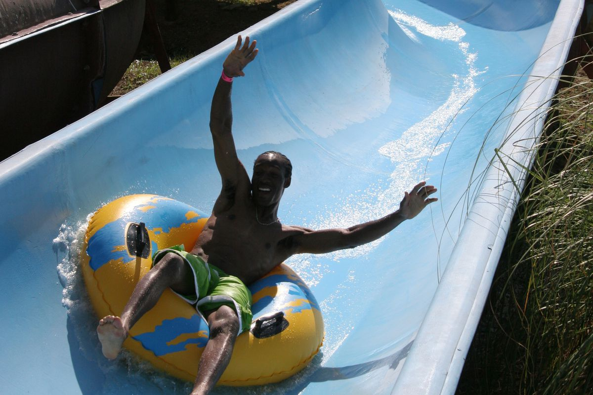 """<p zoompage-fontsize=""""15"""" style="""""""">A man going down a water slide at a Waterpark in Point Mallard Park."""