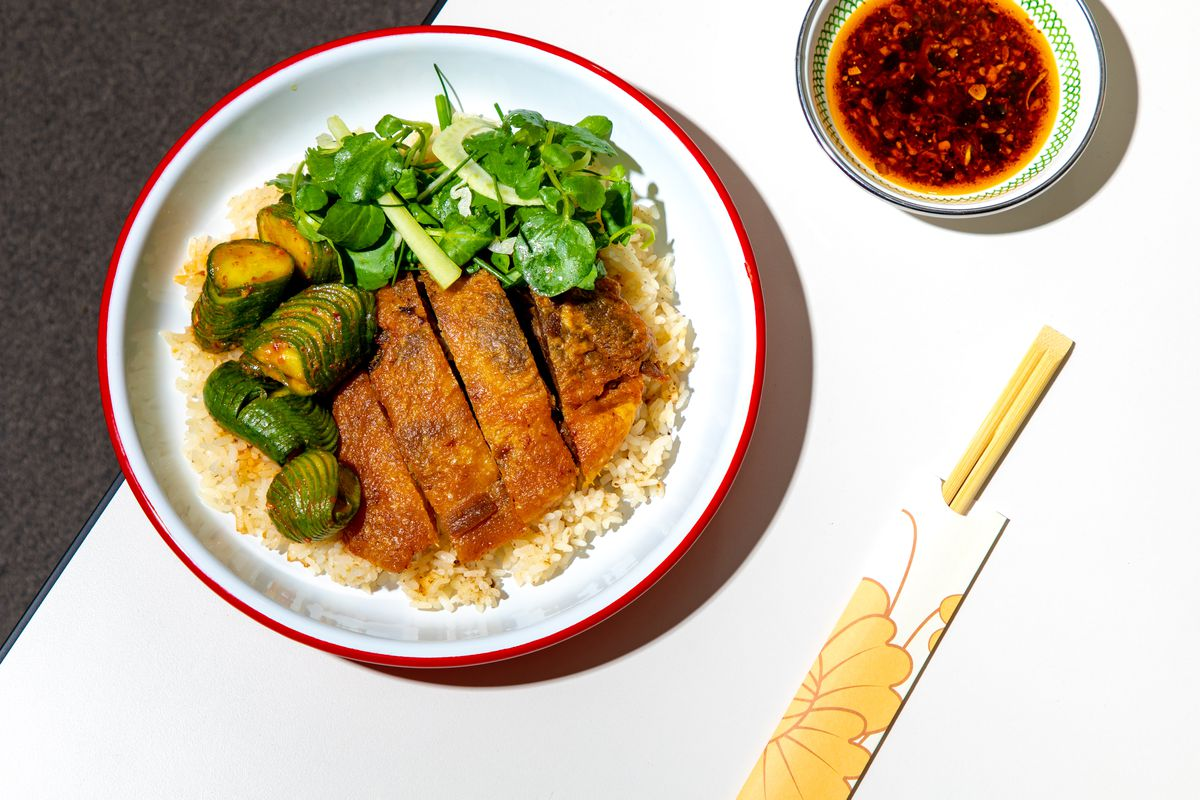Crispy duck leg sits over rice next to a watercress salad and chile cucumbers; a small ramekin of chile crisp sits next to the dish in this overhead shot