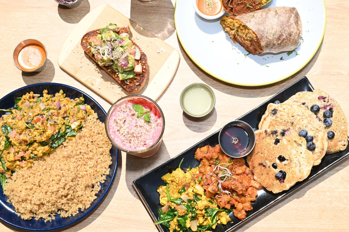 An overhead, extra-sunny shot of vegan Ethiopian food including pancakes and a wrap.