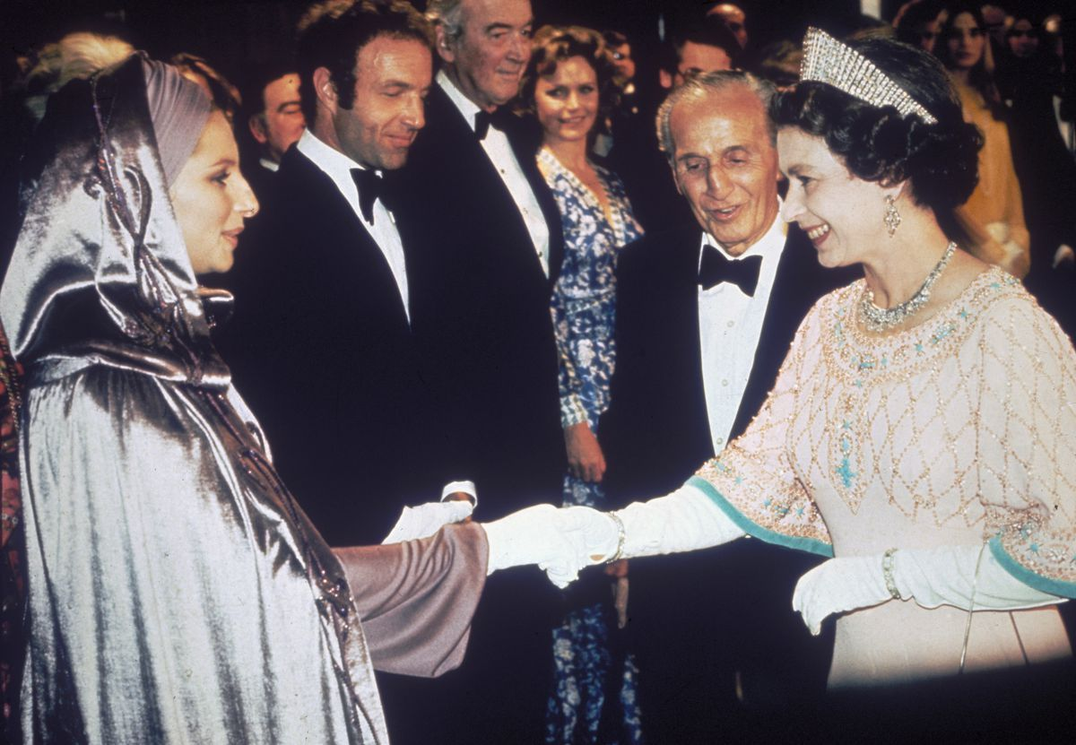 Barbra Streisand and Queen Elizabeth shake hands. Babs wears a silver robe with a hood.