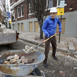Paul Foster, a waiter at Caffe Moilse, shovels debris that fell from the building in Salt Lake City after a 5.7 magnitude earthquake centered in Magna hit early Wednesday, March 18, 2020.